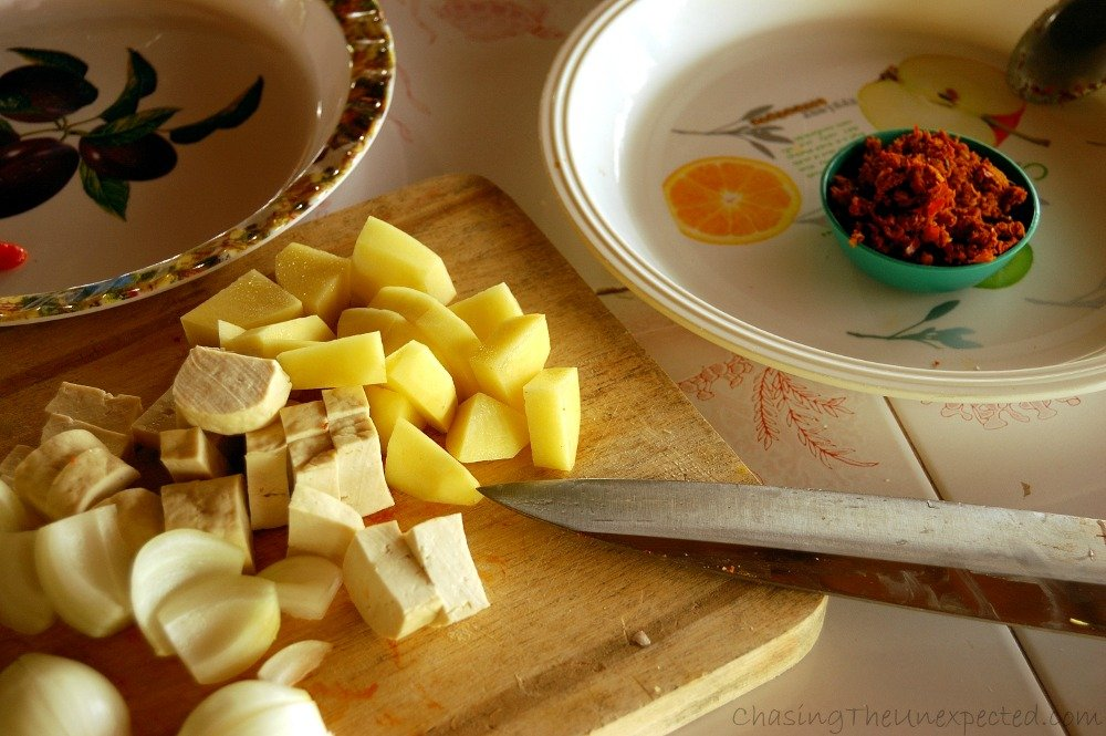 Ready yellow curry paste with chopped tofu and potatoes