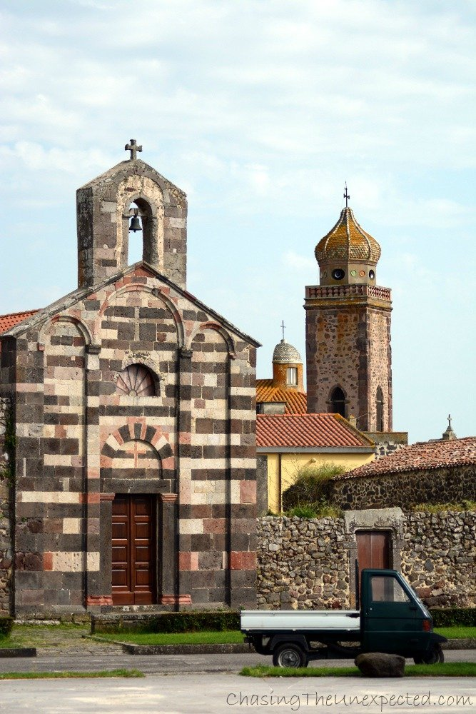 View of ancient San Palmerio church with the bell tower of the main church in the background.